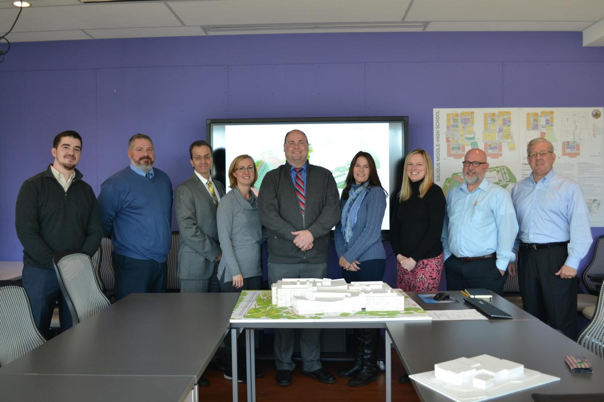 District representatives from Saugus, HMFH Architects, and PMA Consultants pose in front of a model of the future Saugus Middle-